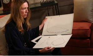 Clare Waight Keller, designer at Givenchy, holds sketches as she gives an interview the day after Meghan Markle walked down the aisle of St George's Chapel in Windsor and married Prince Harry wearing the dress that she created, in Kensington Palace, Londo
