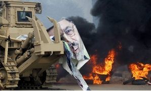A torn poster of deposed Egyptian President Mohamed Morsi is caught on a military vehicle as riot police clear the area of his supporters at Rabaa Adawiya square, where the protesters had been camping, in Cairo. At least 95 Egyptians were killed in ongoin
