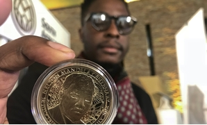 Zimbabwe-born Sindiso Nyoni holds a 1-ounce pure gold 5 rand coin that he designed, as the South African Reserve Bank (SARB) launched a set of limited edition bank notes and gold coins to mark the 100th anniversary of the birth of Nelson Mandela, in Preto
