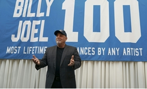 Billy Joel poses under a banner at a press conference to celebrate his achievement of 100 performances at Madison Square Garden in New York-AFP / TIMOTHY A. CLARY