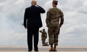"U.S. President Donald Trump salutes a U.S. Army soldier as he observes a military demonstration with U.S. Army Major General Walter ""Walt"" Piatt, the Commanding General of the Army's 10th Mountain Division at Fort Drum, New York, U.S., August 13, 2018. RE"