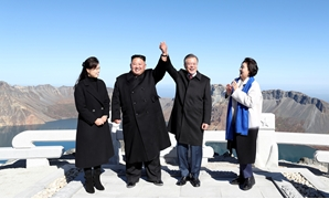 South Korean President Moon Jae-in and North Korean leader Kim Jong Un pose for photographs on the top of Mt. Paektu, North Korea September 20, 2018. Pyeongyang Press Corps/Pool via REUTERS TPX IMAGES OF THE DAY