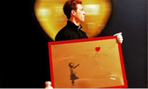 "FILE PHOTO: An employee walks with Banksy's ""Girl and Balloon"" 2009, at Bonhams auction house in London March 23, 2012, REURERS/LUKE MacGregor/File Photo"