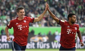 Soccer Football - Bundesliga - VfL Wolfsburg v Bayern Munich - Volkswagen Arena, Wolfsburg, Germany - October 20, 2018 Bayern Munich's Robert Lewandowski celebrates scoring their second goal with Serge Gnabry REUTERS/Fabian Bimmer DFL regulations prohibit