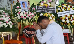 A mourner prays in front of a portrait of 13-year-old Muay Thai boxer Anucha Tasako next to his coffin during a funeral at a Buddhist temple in Samut Prakan province on November 14, 2018. Thais have reacted with shock and anger after Tasako died during a