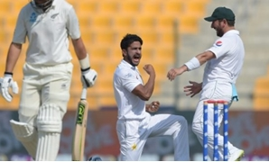 © AFP | Pakistan's Hasan Ali (C) celebrates with Yasir Shah after taking the wicket of New Zealand's Ross Taylor (L) during the third day of the first Test