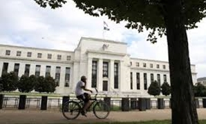 FILE PHOTO: A cyclist passes the Federal Reserve building in Washington, DC, U.S., August 22, 2018. REUTERS/Chris Wattie/File Photo/File Photo