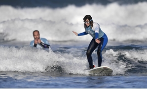 Carmen Lopez Garcia, Spain's first blind female surfer who is to participate in the ISA World Adaptive Surfing Championship, is watched by her coach Lucas Garcia during training at Salinas beach, Spain, December 6, 2018. REUTERS/Eloy Alonso