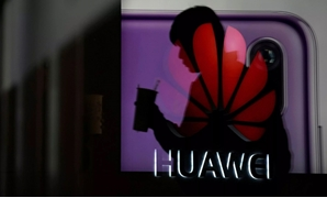 A man walking past a Huawei P20 smartphone advertisement is reflected in a glass door in front of a Huawei logo, at a shopping mall in Shanghai, China December 6, 2018. - Aly Song | Reuters