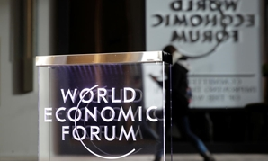 A person passes by a World Economic Forum logo in Davos, Switzerland, January 20, 2019. REUTERS/Arnd Wiegmann