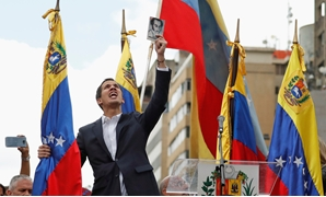 Juan Guaido, President of Venezuela's National Assembly, holds a copy of Venezuelan constitution during a rally against Venezuelan President Nicolas Maduro's government and to commemorate the 61st anniversary of the end of the dictatorship of Marcos Perez
