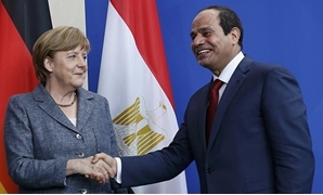 FILE - German Chancellor Angela Merkel and Egypt's President Abdel Fattah al-Sisi shake hands