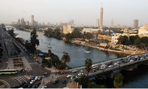 Cars crisscross through the inner city of Cairo Egypt, alongside the Nile River during the day. Cairo is the capital of Egypt and the largest city in Africa as well as one of the most densely populated cities in the world. Cairo is the center of the regio