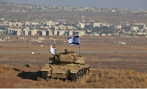 An Israeli flag flutters over the wreckage of an Israeli tank overlooking the armistice line on the Golan Heights.