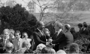 Anwar Sadat, Jimmy Carter, and Menachem Begin shaking hands on the White House grounds – Warren K. Leffler