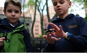 Eight-year-old Tom Wuestenberg (L) and his ten-year-old brother Louis play with fidget spinners - AFP/JEWEL SAMAD