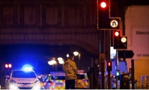Police vehicles and a police officer are seen outside the Manchester Arena - REUTERS