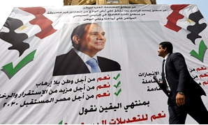 "A man walks in front of a banner reading, ""Yes to the constitutional amendments, for a better future"", with a photo of the Egyptian President Abdel Fattah al-Sisi before the approaching referendum on constitutional amendments in Cairo, Egypt April 16, 201"