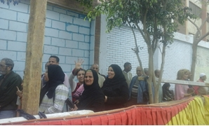 Queues of voters lined up outside polling stations in Giza to vote in referendum - Press Photo