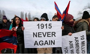 "An Armenian protester holds a sign reading ""1915 never again"" as she takes part in a demonstration near the European Court of Human Rights in Strasbourg, on Jan 28, 2015. — Reuters"