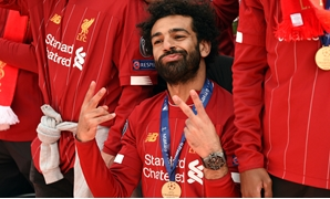 Liverpool's Egyptian midfielder Mohamed Salah gestures to the fans during an open-top bus parade around Liverpool, north-west England on June 2, 2019, after winning the UEFA Champions League final football match between Liverpool and Tottenham. Liverpool'