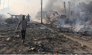 Civilians evacuate from the scene an explosion at KM4 street in the Hodan district in Mogadishu