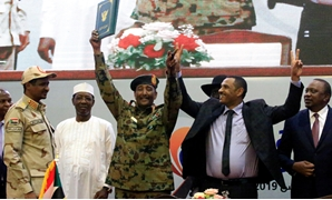 Sudan's Head of Transitional Military Council, Lieutenant General Abdel Fattah Al-Burhan, and Sudan's opposition alliance coalition's leader Ahmad al-Rabiah, celebrate the signing of the power sharing deal, that paves the way for a transitional government