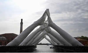 A general view shows the Italian artist Lorenzo Quinn's Building Bridges, a sculptural installation showing six pairs of arching hands creating a bridge over a Venetian waterway in the Arsenal former shipyard, in Venice on May 8, 2019. Tiziana Fabi / AFP