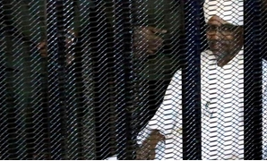 Sudan's former president Omar al-Bashir sits guarded inside a cage at the courthouse where he is facing corruption charges, in Khartoum, Sudan August 19, 2019. (Reuters)