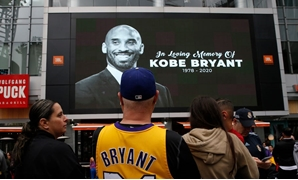 Kobe Bryant on screen in public square - file