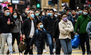 Pedestrians wearing face masks cross a road during a Lunar New Year of the Rat public holiday in Hong Kong on January 27, 2020, as a preventative measure following a coronavirus outbreak which began in the Chinese city of Wuhan