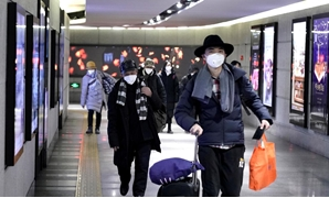 FILE PHOTO: People wearing masks walk through an underground passage to the subway in Beijing, China January 21, 2020. REUTERS/Jason Lee/File Photo