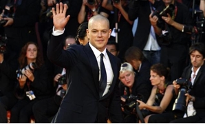 "FILE PHOTO: Actor Matt Damon (R), cast member of the movie ""Contagion"", waves as he arrives on the red carpet at Cinema Palace during the 68th Venice Film Festival September 3, 2011. REUTERS/Alessandro Bianchi."