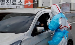 FILE PHOTO: A medical staff member in protective gear prepares to take samples from a visitor at a 'drive-thru' testing center for the novel coronavirus disease of COVID-19 in Yeungnam University Medical Center in Daegu, South Korea, March 3, 2020. REUTER