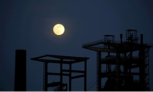 FILE PHOTO: The pink supermoon rises behind the ruin of a blast furnace of the former Phoenix West steel mill in Dortmund, Germany, April 7, 2020. REUTERS/Leon Kuegeler