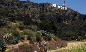 FILE PHOTO: People hike beneath the Hollywood sign after a partial reopening of Los Angeles hiking trails during the outbreak of the coronavirus disease (COVID-19) in Los Angeles, California, U.S., May 9, 2020. REUTERS/Patrick T. Fallon/File Photo.