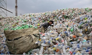 A man pulls a sack filled with empty bottles at a plastic junkyard in Chandigarh, June 5, 2015. REUTERS/Ajay Verma